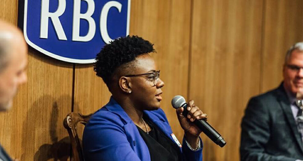 Ketty Cédat speaking into microphone at an RBC event